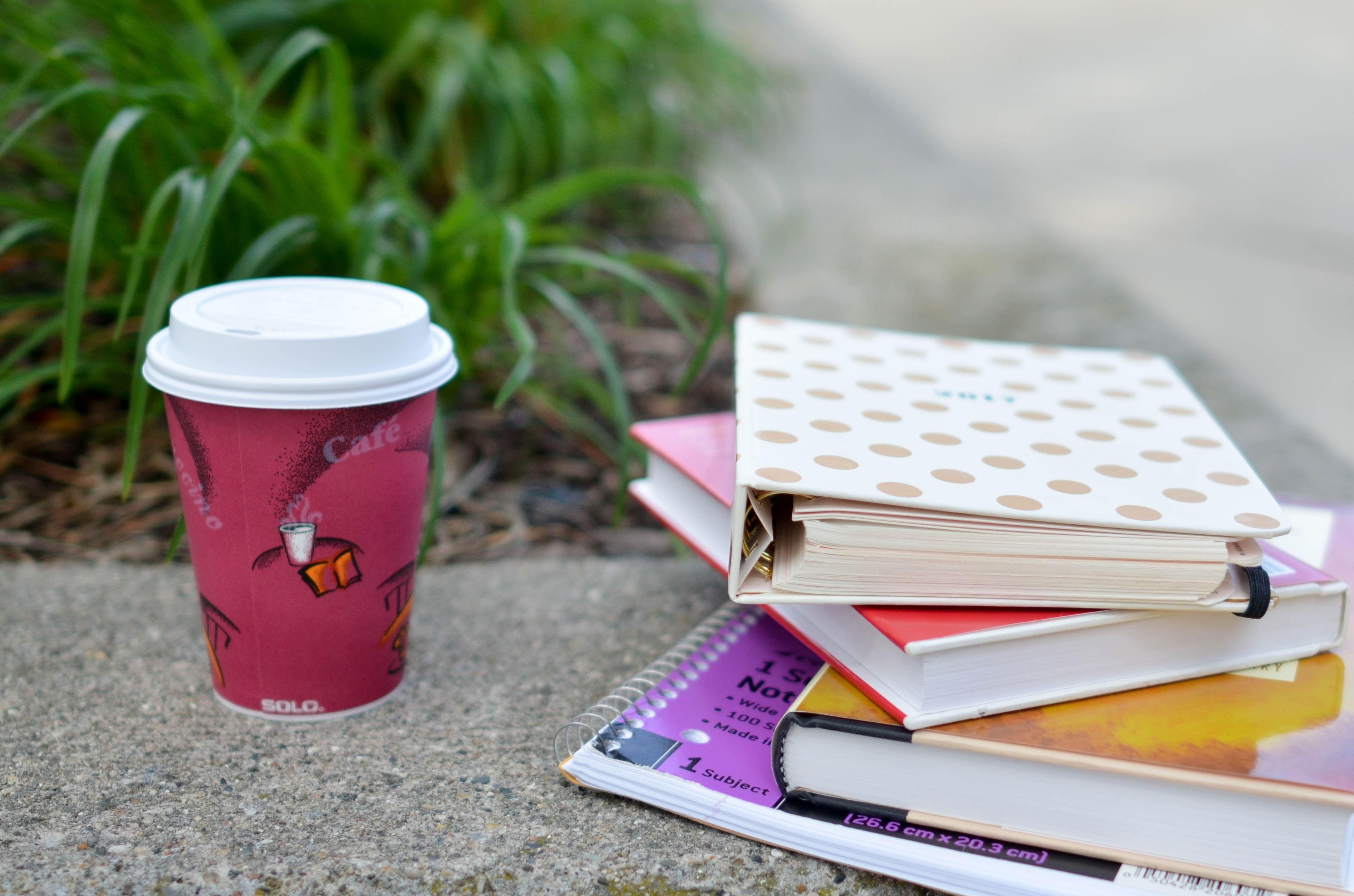 Kaffeebecher, Bücher und Notizbücher auf sandiger Unterlage