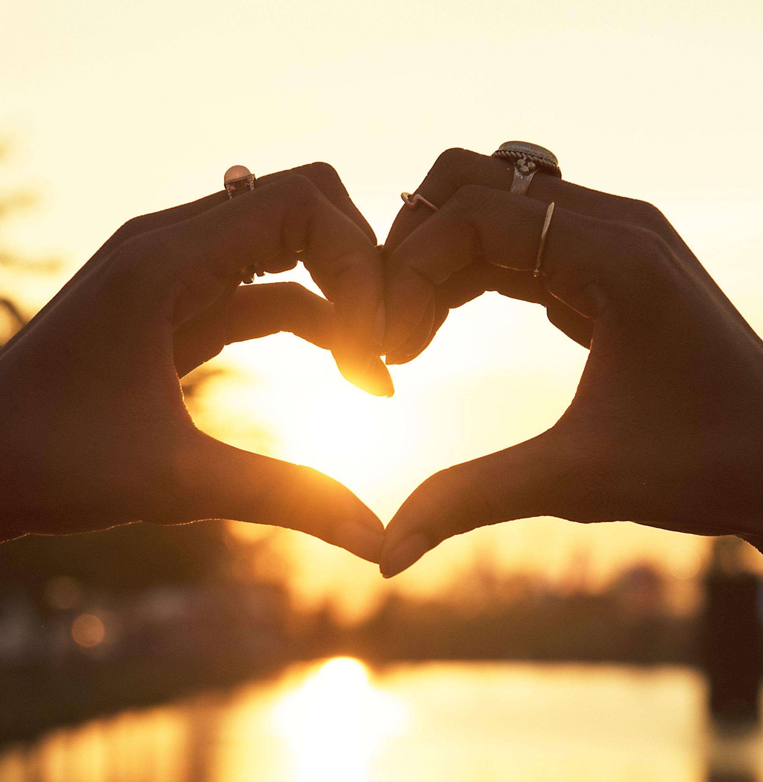Hände formen ein Herz im Sonnenlicht.