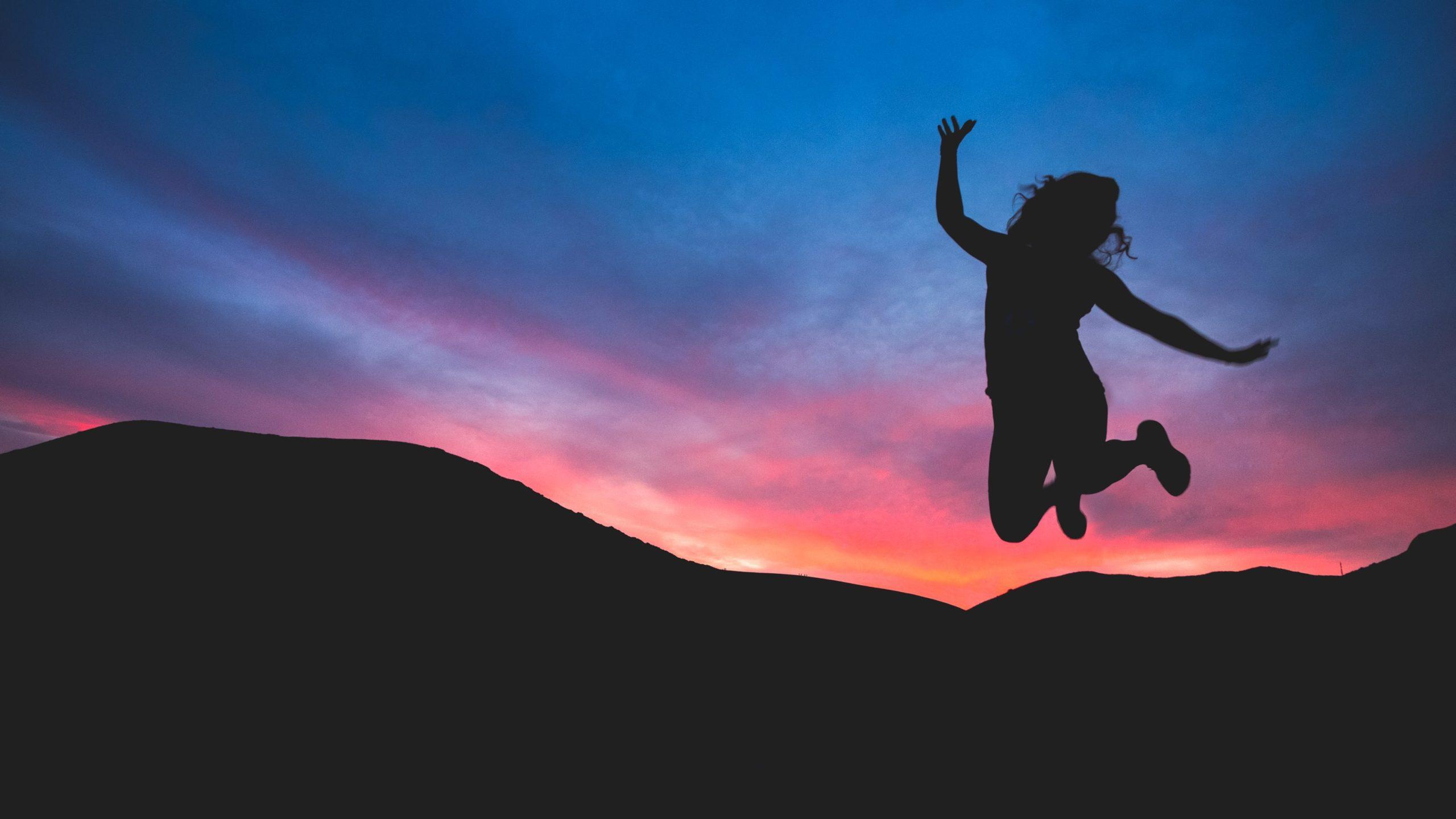Silhouette einer Frau, die im Sonnenuntergang über eine Berg-Silhouette springt und Freude ausdrückt.